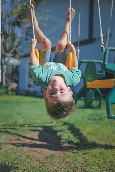 blonde boy upside down on swing set photo