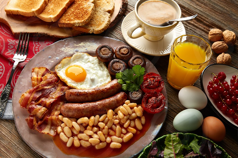 English breakfast with sausages egg beans bacon mushrooms and grilled tomato photo