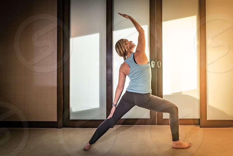 Beautiful young woman stretching relaxing and doing yoga exercises photo