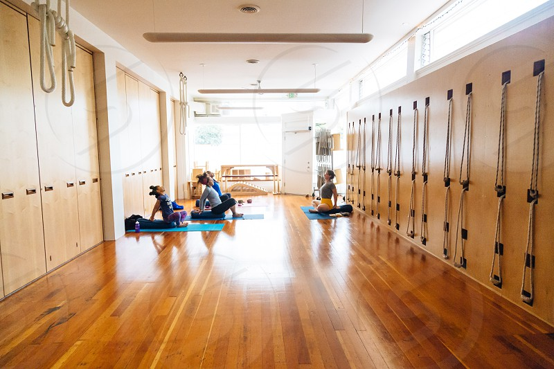 people sitting on yoga mat on parquet floor during daytime photo