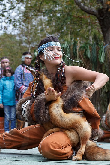 KAMCHATKA PENINSULA RUSSIA - SEP 14 2013: Public concert on Itelmen national holiday of thanksgiving nature Alhalalalay. Expression young woman (ensemble Northern Dawns) dancing in clothing aborigine of Kamchatka Peninsula. photo