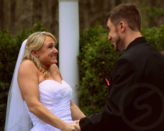 lady in wedding gown holding a man hand photo