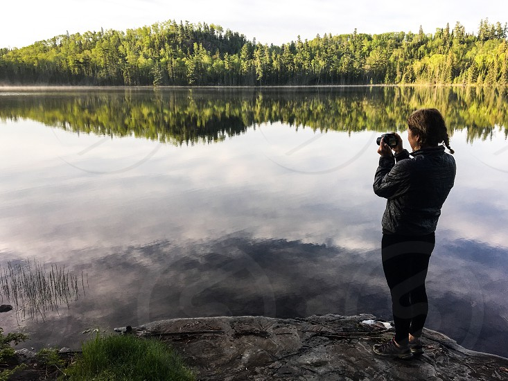 Hiker taking picture of lake photo