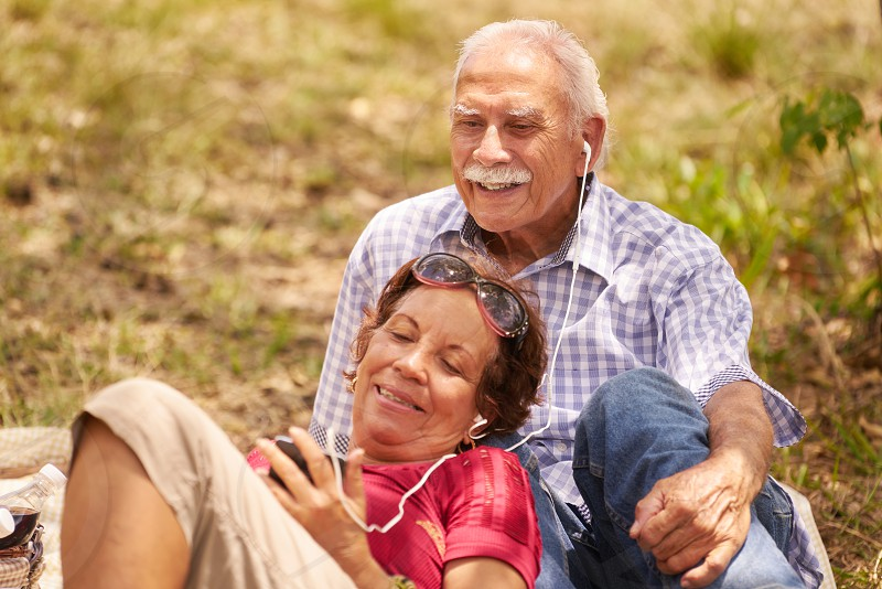 Old people senior couple elderly man and woman in park. Grandpa and grandma listening to song music with mp3 player photo