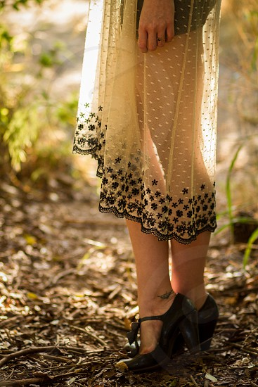 A young woman standing in profile as the sun shines through her spotted lace dress photo