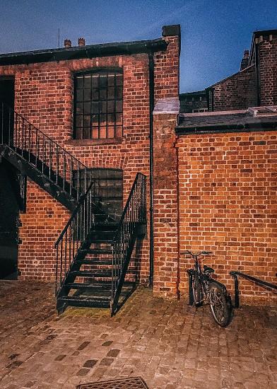 black metal outdoor staircase attach brown and orange brick wall near black cruiser bike photo