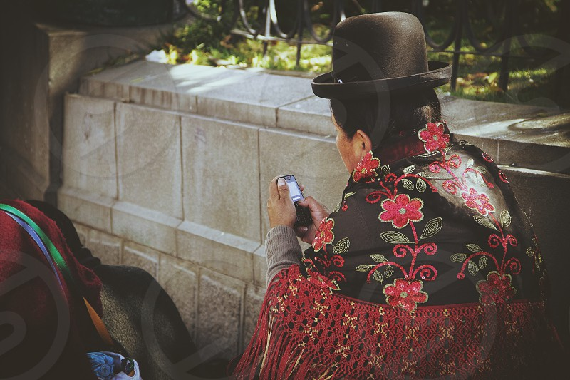 Woman sending a text message La Paz Bolivia. Post processed with VSCOcam's M3 filter. photo
