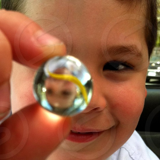 boy with dark hair holding up clear marble with yellow streak photo