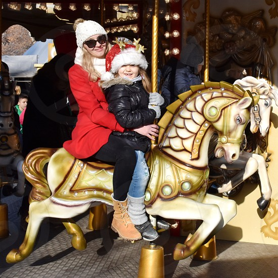 Closeup of mother and child riding on the carousel horse during Christmas holidays photo