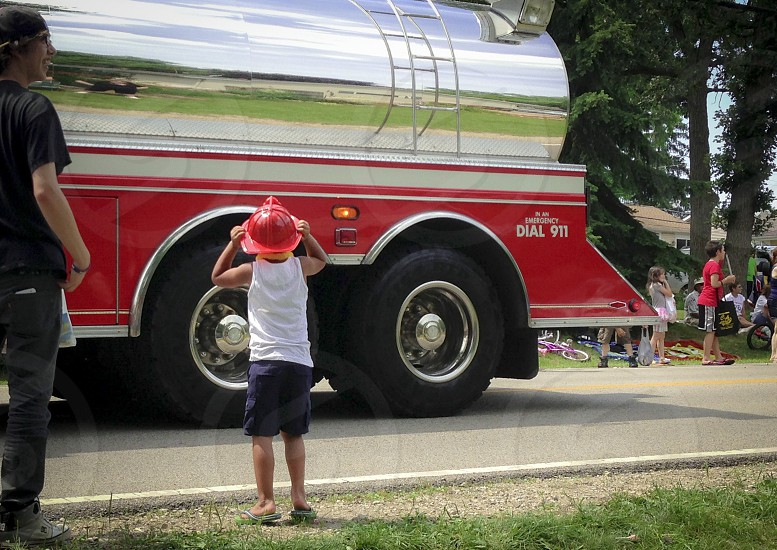 Little boy at Fourth of July parade putting on toy fire hat watching firetrucks go by. Accompanied by a teenage guy. photo