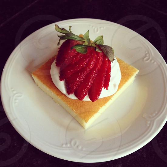 Japanese Cheese Cake with Whipped Cream and Fanned Strawberry.  photo