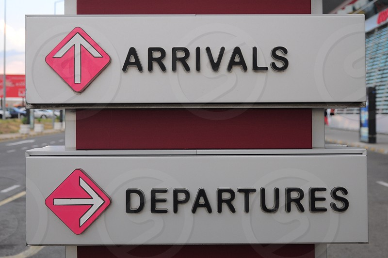 arrival straight ahead and departures to the left sign photo