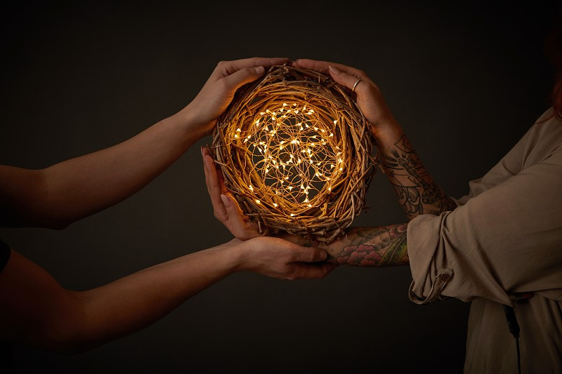 Male hands and woman hands with tattoos holding a bright wreath of twigs with yellow garlands around a black background with copy space for text. Romantic concept photo