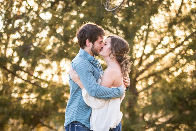 man in blue long sleeve shirt kissing a woman in white off shoulder dress near trees photo