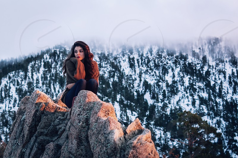woman sitting rock by the mountain top with mountain alps behind photo