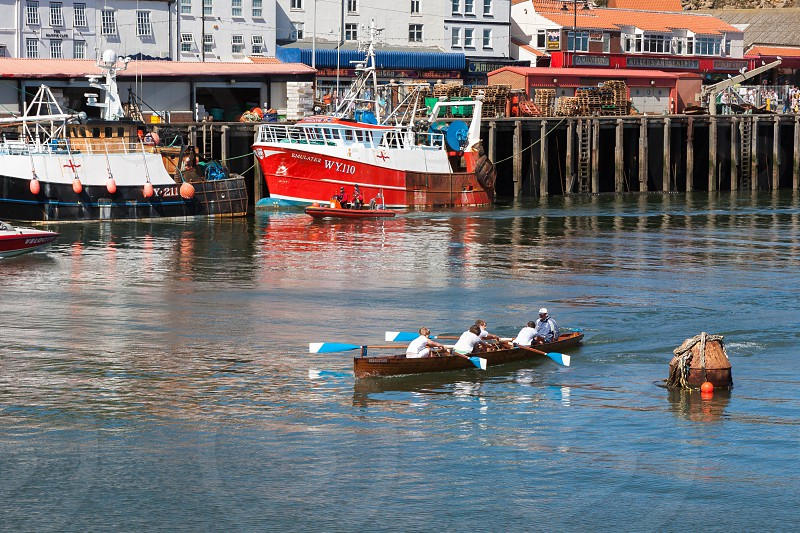 Unidentified man and boys exhausted at the end of a rowing boat race in Whitby photo