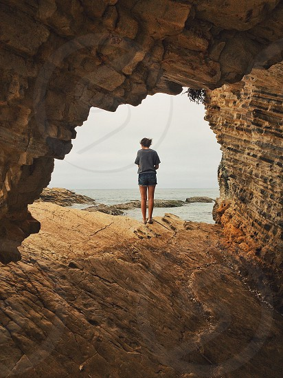 woman standing in front of cave facing ocean at daytime photo
