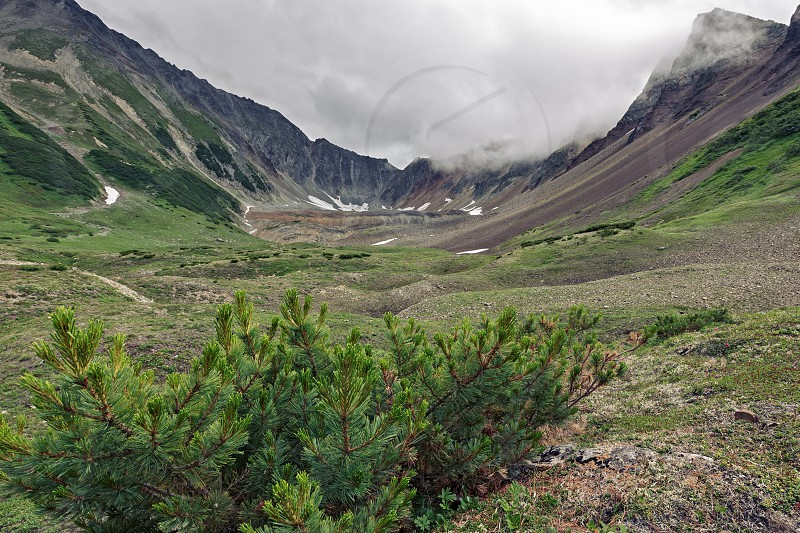 Summer mountain landscape of Kamchatka Peninsula: beautiful view of Mountain Range Vachkazhets - mountain circus with rocky slopes in overcast weather. Eurasia Russian Far East Kamchatka Region. photo