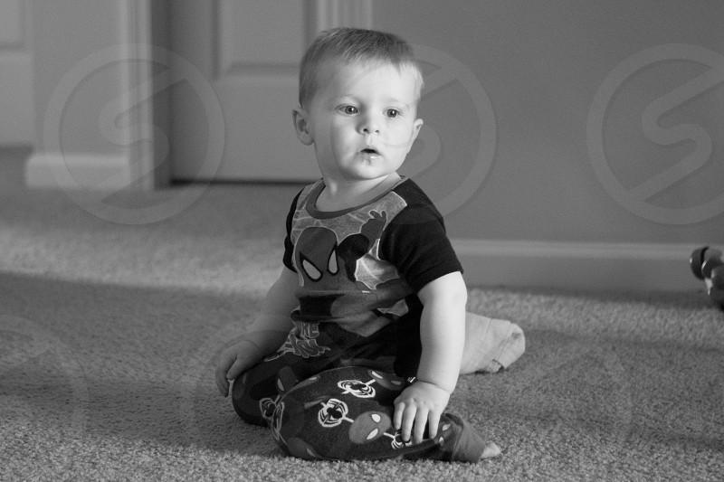 boy in spiderman printed shirt sitting on floor photo