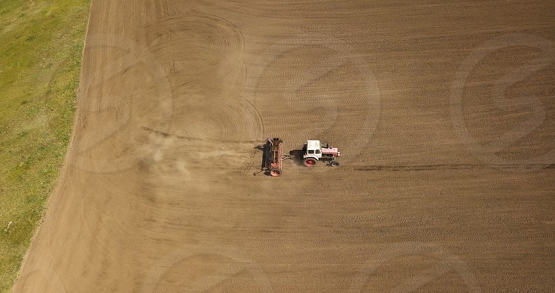 Aerial view of working tractor with trailer over an agricultural field. Industrial background on agricultural theme. Photo by drone photo