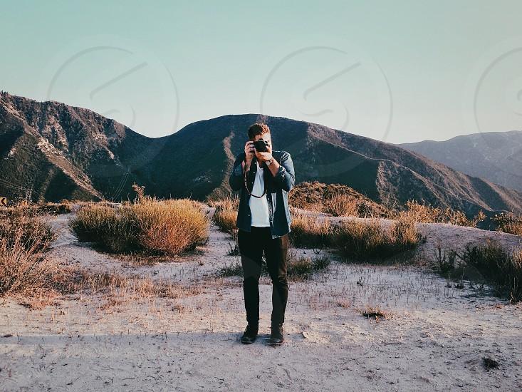 man in black jacket holding camera photo