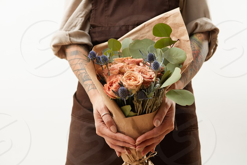 Young girl in a brown apron holds beautiful bunch with fresh natural flowers living coral colored and green leaves on a light background copy space. Holiday congratulation card. photo