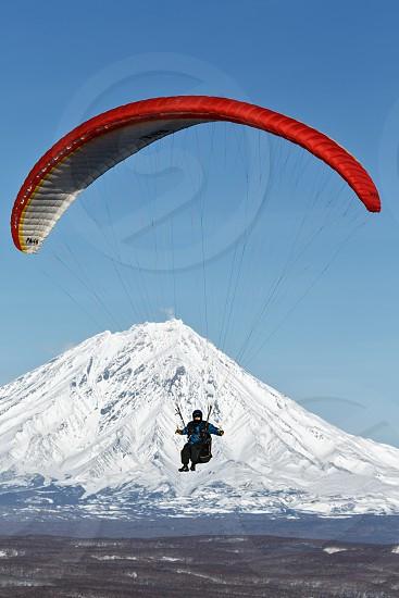 KAMCHATKA PENINSULA RUSSIA - NOVEMBER 21 2014: Paraglider flying on the background of the active Koriaksky Volcano (Koryaksky Volcano) on a sunny day. photo