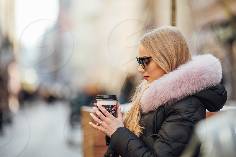 Pretty girl wear sunglasses and drink coffee on the street photo