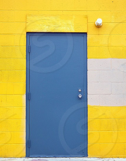 Blue metal door on a building with painted yellow cement blocks. photo
