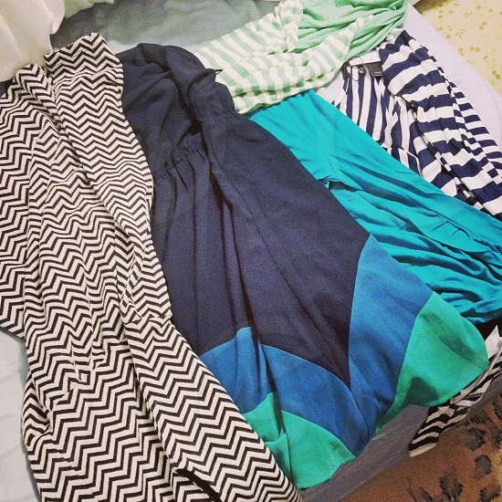 Clothing laid out on a bed | patterns stripes chevron fabric teal green blue photo