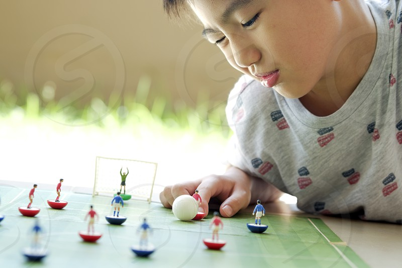 Close-up of a young boy playing table soccer. Shallow depth of field. Focus on foreground. photo