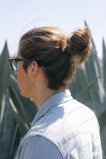 person wearing black framed eyeglasses and beige collared shirt with ponytail hair photo