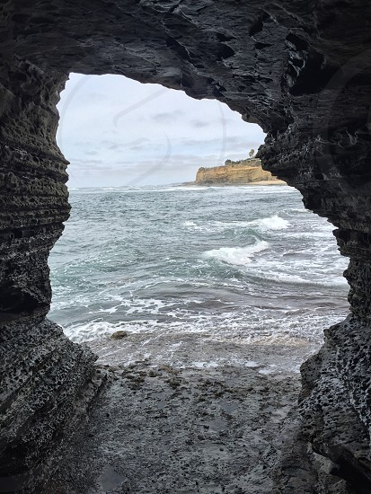 gray cave near body of water under white sky photo