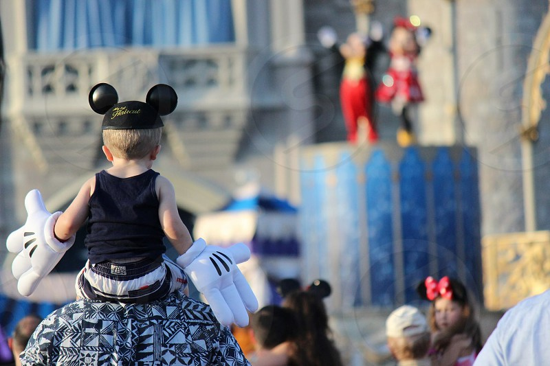 selective focus photography of man carrying child wearing mickey mouse costume photo
