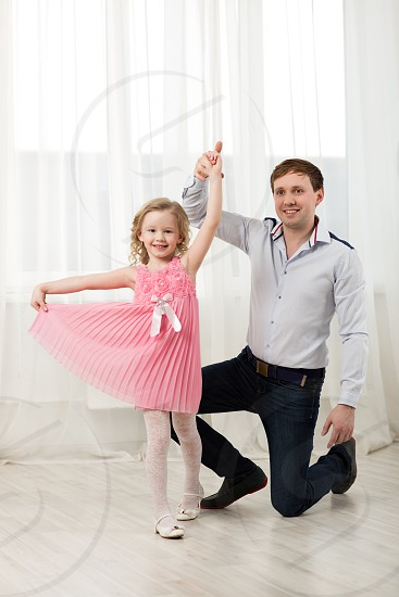 Father and little daughter dancing. Little princess in pink dress walking around dad standing on knee photo