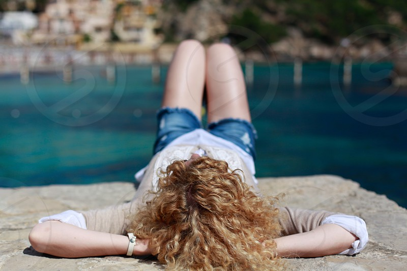 woman in brown and white long sleeve shirt and blue distressed denim shorts lying on brown rock by the body of water photo
