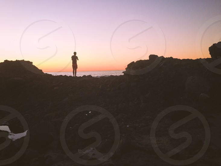 man standing on rock silhouette photo