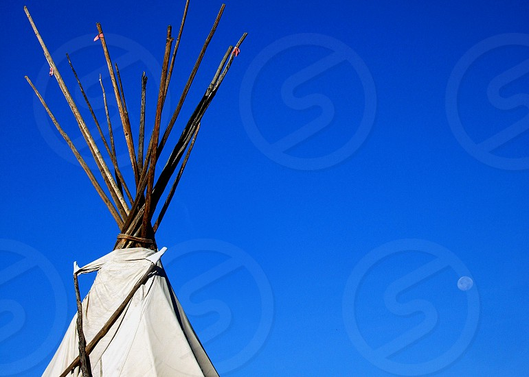 Native American Tipi against a blue sky and daytime moon photo