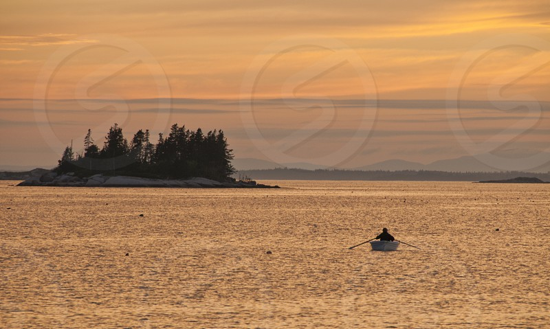 person rowing boat on sea photo
