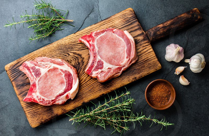 Raw pork cutlet chop for fry on pan with herbs garlic on wooden boards slate gray background. photo