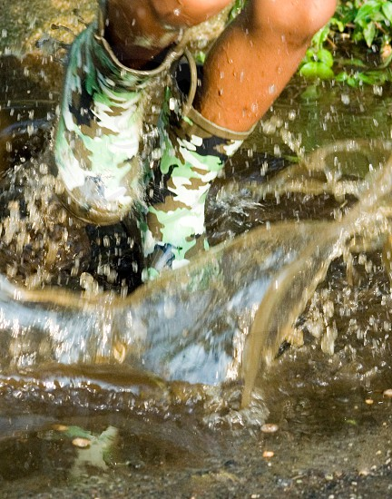 person wearing green black brown and white camouflage boots walking in water during daytime photo