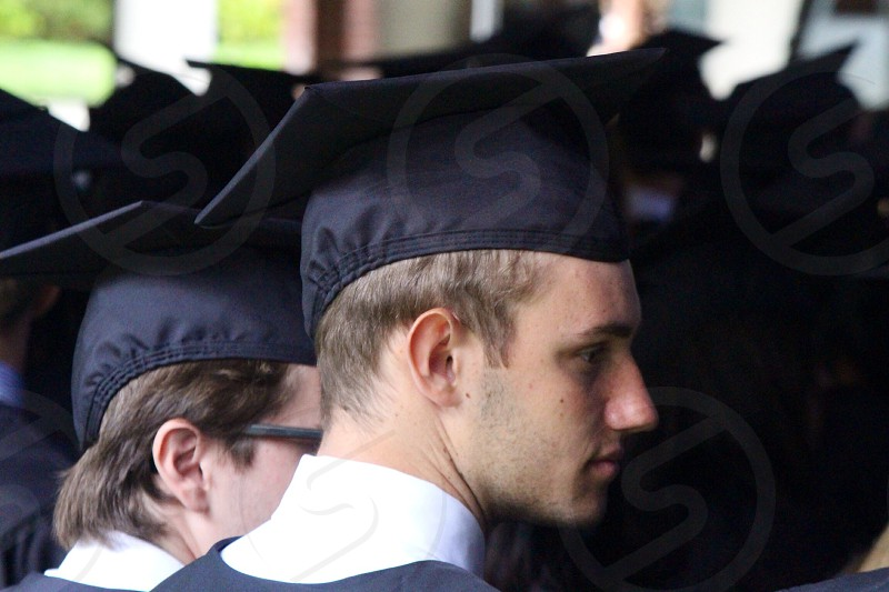 man wearing black and white graduation uniform with black cap photo