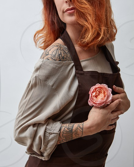 Cute girl with a tattoo holds in her hand a pink flower of a Ranunculus on a gray background. Mother's Day photo