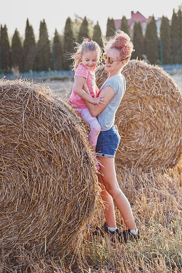 Sisters teenage girl and her younger sister playing together on hay bale outdoors in the field in the countryside. Candid people real moments authentic situations photo