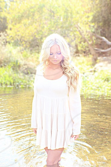 woman wearing a white dress standing in water photo