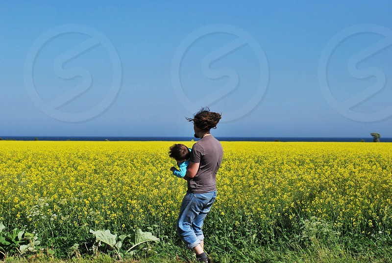 woman carrying a baby on a yellow flower field photo