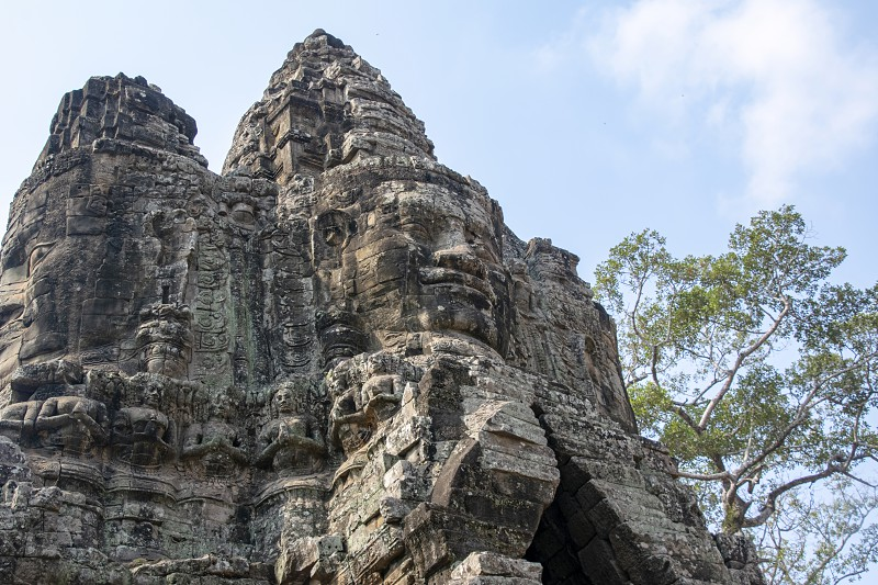 Cambodia Bayon Temple - March 2016: The temple bridge is a main through road for traffic. Carved like the Bayon temple with a multitude of serene and smiling stone faces  photo