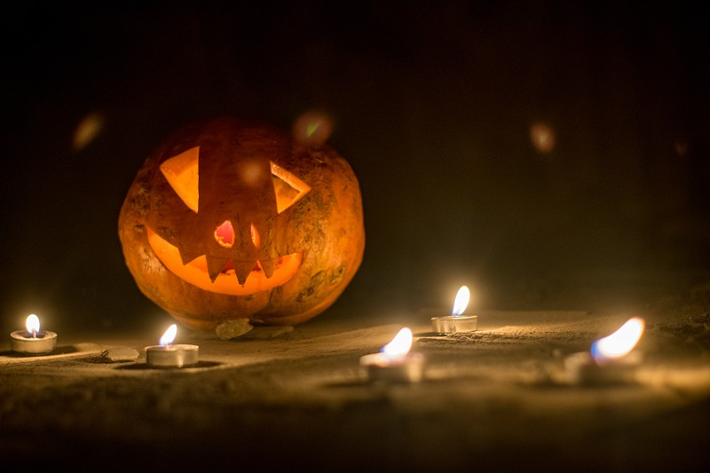 Scary halloween pumpkin surrouned by little candles in the dark low angle view photo