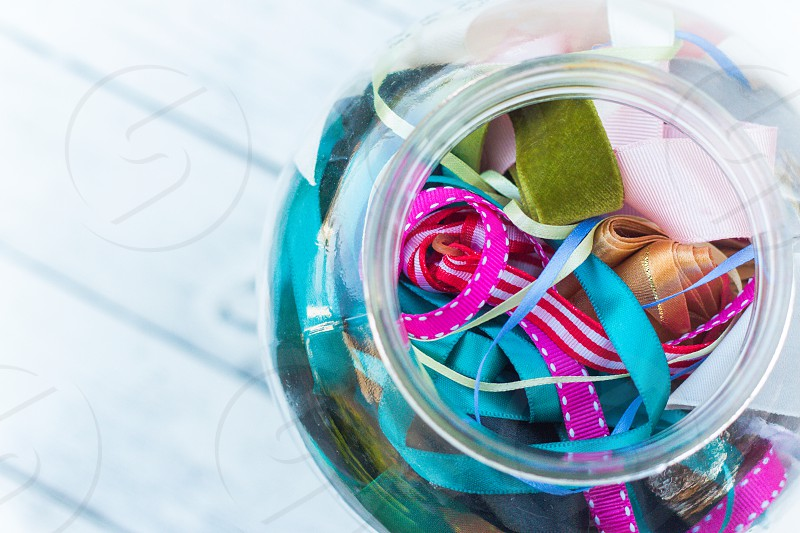 A glass jar full of different coloured ribbons photo