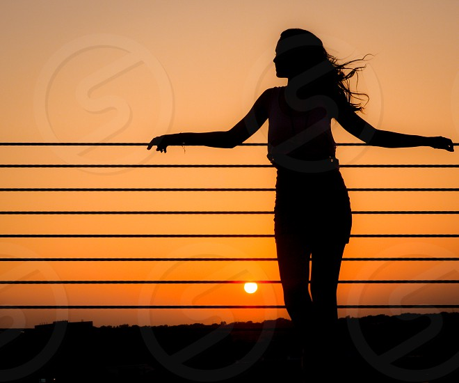 Vibrant sunset over land with a nice breeze catching her hair. photo